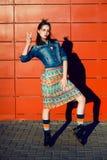 Jeune fille d'adolescent ayant l'amusement, posant et souriant près du fond rouge de mur dans la jupe et la veste de jeans sur le Images stock