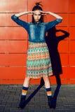 Jeune fille d'adolescent ayant l'amusement, posant et souriant près du fond rouge de mur dans la jupe et la veste de jeans sur le Image libre de droits