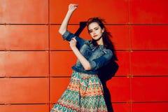 Jeune fille d'adolescent ayant l'amusement, posant et souriant près du fond rouge de mur dans la jupe et la veste de jeans sur le Photo stock