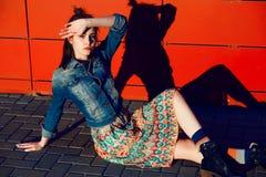 Jeune fille d'adolescent posant et s'asseyant près du fond rouge urbain de mur dans la jupe et la veste de jeans sur le coucher d Image libre de droits