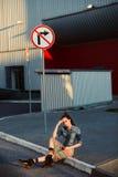 Jeune fille d'adolescent s'asseyant sur la route en dehors du fond rouge urbain proche de mur dans la jupe et la veste de jeans s Image stock