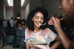 Jeune fille d'Afro-américain mangeant le gâteau dans le restaurant Jeune homme alimentant son amie au café Belle dame avec Photographie stock libre de droits
