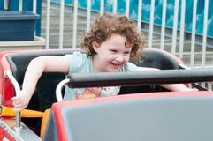 Jeune fille d'enfant en bas âge ayant l'amusement sur le tour d'amusement de promenade Photos stock