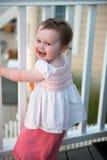 Jeune fille d'enfant en bas âge sur la plate-forme de patio dehors au coucher du soleil vers le bas au rivage Photographie stock libre de droits