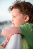 Jeune fille d'enfant en bas âge sur la plate-forme de patio dehors au coucher du soleil vers le bas au rivage Photo stock
