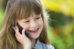 Jeune fille d'enfant mignon parlant sur le t?l?phone portable dehors Enfants et technologie moderne, concept de communication photos libres de droits