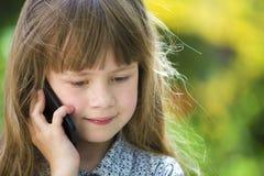 Jeune fille d'enfant mignon parlant sur le t?l?phone portable dehors Enfants et technologie moderne, concept de communication photographie stock libre de droits