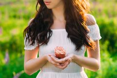 Jeune fille d'une chevelure foncée tenant un petit pain rose-écrémé photo libre de droits