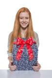 Jeune fille d'une chevelure rouge présent un cadeau Image libre de droits