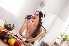Jeune fille dans des écouteurs à la position saine de mode de vie de cuisine écoutant la chanson de chant de musique l'aubergine photos stock