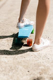 Jeune fille dans des espadrilles sur la planche à roulettes Image stock