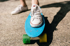 Jeune fille dans des espadrilles sur la planche à roulettes Photo libre de droits
