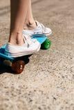 Jeune fille dans des espadrilles sur la planche à roulettes Photographie stock libre de droits