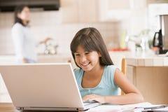Jeune fille dans la cuisine avec l'ordinateur portatif et les écritures image libre de droits