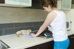 Jeune fille dans la cuisine avec le chien Image stock
