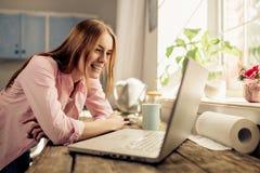 Jeune fille dans la cuisine, souriant regardant l'ordinateur portable Images libres de droits