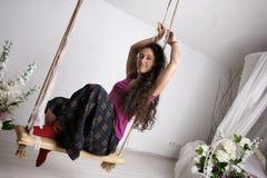 Jeune fille dans la longue jupe se reposant sur l'oscillation dans la chambre blanche Images stock