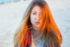 Jeune fille dans la lumière de coucher du soleil Femme avec le long sourire de cheveux Le visage d'une jeune fille dans une lumiè Photos stock