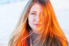 Jeune fille dans la lumière de coucher du soleil Femme avec le long sourire de cheveux Le visage d'une jeune fille dans une lumiè Image stock