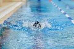 Jeune fille dans la natation de chapeau dans la piscine d'eau bleue Photo stock
