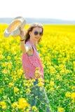 Jeune fille dans la robe ? carreaux rouge et chapeau de soleil posant dans le domaine de colza ol?agineux image libre de droits