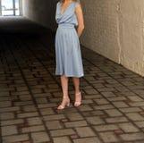 Jeune fille dans la robe d'été dans des espadrilles légères sur la pose de rue Images stock