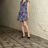 Jeune fille dans la robe d'été dans des espadrilles légères sur la pose de rue Photographie stock
