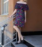 Jeune fille dans la robe d'été dans des espadrilles légères sur la pose de rue Photos stock