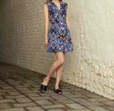 Jeune fille dans la robe d'été dans des espadrilles légères sur la pose de rue Photos libres de droits