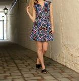 Jeune fille dans la robe d'été dans des espadrilles légères sur la pose de rue Images libres de droits