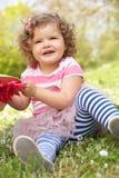 Jeune fille dans la robe d'été se reposant dans le domaine Image stock