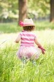 Jeune fille dans la robe d'été se reposant dans le domaine Photo stock