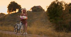 Jeune fille dans la robe marchant sur la route avec le vélo et les fleurs banque de vidéos