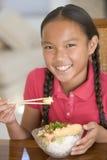 Jeune fille dans la salle à manger mangeant de la nourriture chinoise Photographie stock libre de droits