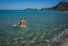 Jeune fille dans le bikini rouge jouant avec l'eau de mer Photos libres de droits