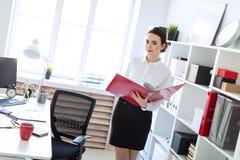 Jeune fille dans le bureau près du support et des parcourir le dossier avec les documents photographie stock