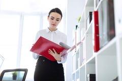 Jeune fille dans le bureau près du support et des parcourir le dossier avec les documents photos stock