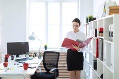 Jeune fille dans le bureau près du support et des parcourir le dossier avec les documents photo stock