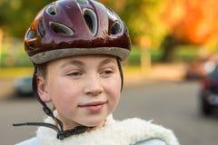 Jeune fille dans le casque s'usant de bicyclette d'automne Photo stock