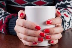 Jeune fille dans le chandail jugeant la tasse de café blanc disponible avec les clous rouges sur le bureau en bois Images libres de droits