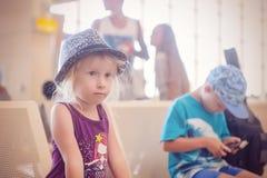Jeune fille dans le chapeau attendant dans l'aéroport avec la famille Images stock