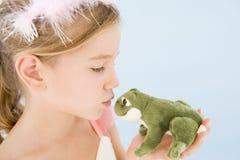 Jeune fille dans le costume de princesse embrassant la grenouille de peluche Photos stock