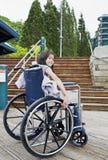 Jeune fille dans le fauteuil roulant devant des escaliers Photographie stock libre de droits