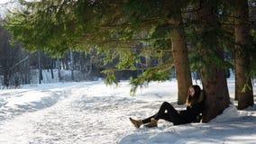 Jeune fille dans le manteau noir reposant sur la correction dégelée un arbre dans la neige dans une forêt sauvage fabuleuse Photo stock