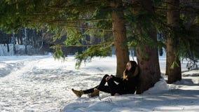 Jeune fille dans le manteau noir reposant sur la correction dégelée un arbre dans la neige dans une forêt sauvage fabuleuse Image stock