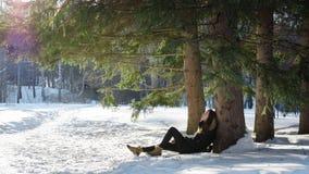 Jeune fille dans le manteau noir reposant sur la correction dégelée un arbre dans la neige dans une forêt sauvage fabuleuse Images stock