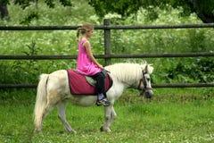 Jeune fille dans le poney rose d'équitation Image libre de droits