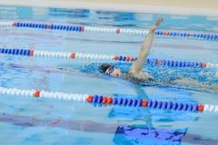 Jeune fille dans les lunettes et chapeau nageant le style de course de rampement avant dans la piscine d'eau bleue Image libre de droits