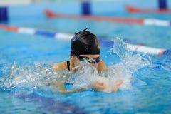 Jeune fille dans les lunettes et style de course de papillon de natation de chapeau dans la piscine d'eau bleue Images stock