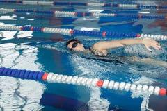 Jeune fille dans les lunettes et style de course de rampement de natation de chapeau dans la piscine d'eau bleue Photos stock